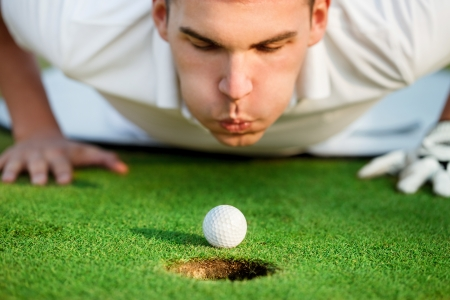 by blowing:  golfer lying on grass and blowing in the ball,  just need to give it a little help. Stock Photo