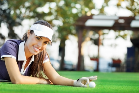 Female golfer cheating by pushing ball in hole photo