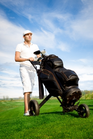 Handsome young golfer out on the course with his clubs and bag photo