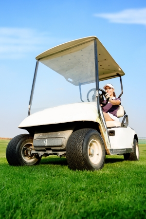 Young female golfer driving golf cart photo