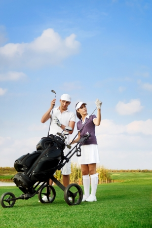 young couple playing golf at the club, choosing  sticks out of the golf-bag photo