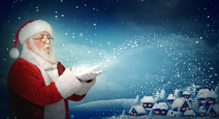 Santa Claus blowing snow to blue  little town at night Stock Photo