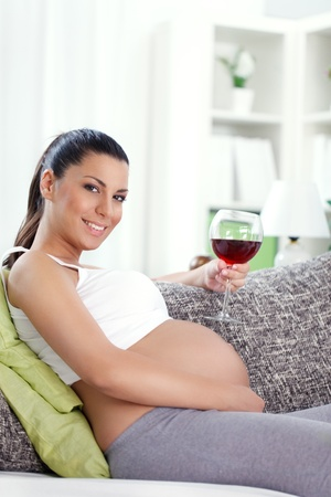 pregnant relaxing on sofa: pregnant woman drinking glass of  wine at home