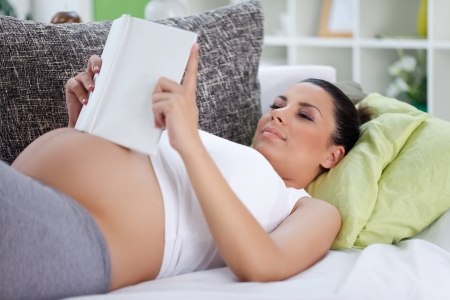 pregnant woman lying on couch relaxing and reading book photo