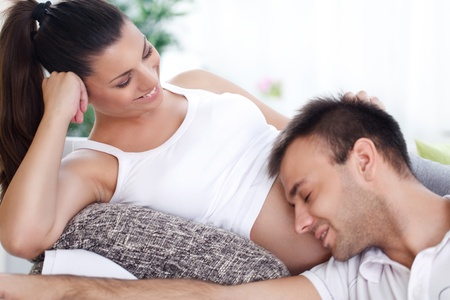 home birth:  Happy future dad listening the belly of his pregnant wife Stock Photo