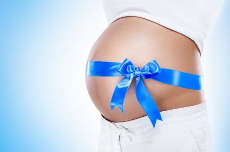 Pregnant belly with blue ribbon, isolated on white background  photo