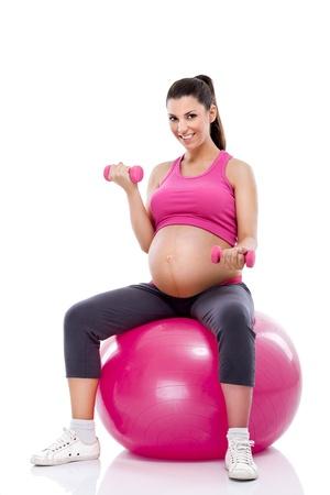 levantando pesas: mujer embarazada haciendo ejercicios de b�ceps con pesas m�sculo mientras est� sentado en una bola de la aptitud Foto de archivo