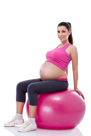 pregnancy exercise:  pregnant woman sportswear with large belly  sitting on fitness ball   Stock Photo
