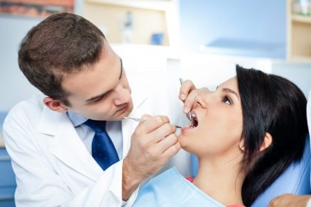 Female patient with dentist and assistant - dental treatment Stock Photo - 16860966
