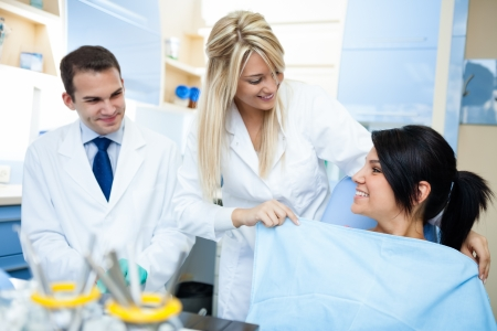 stomatologist: Dentist assistant is putting the protection on patient