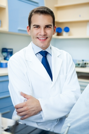 laboratory coat:  Handsome cheerful young dentist