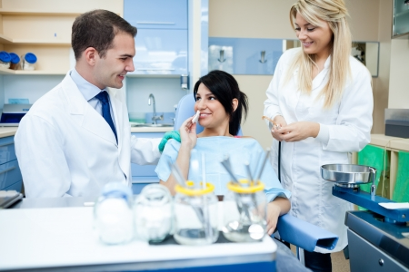 Smiling dental team with patient after treatment Stock Photo - 16860983