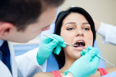 Dentist with mirror checking patient's teeth Stock Photo - 16860997