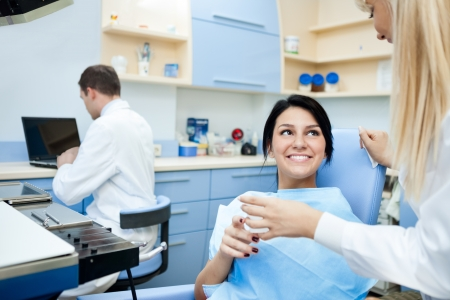 dental examination:  Smiling patient at the dentist office after treatment  Stock Photo