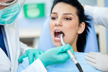 dentists surgery: Feale patient with open mouth during drilling  treatment at the dentist