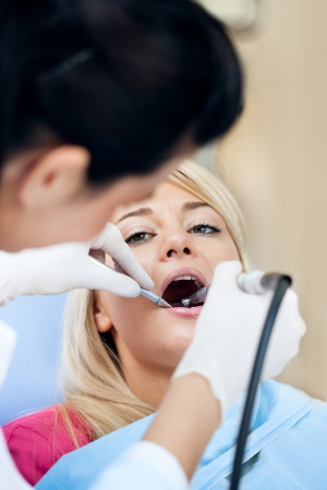 Young woman having her teeth polished by a dental hygienist photo