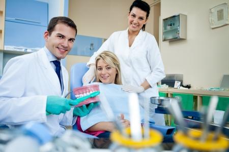 comunicacion oral: Dentista demostrar cepillo de dientes en la oficina de la clínica dental - concepto de educación dental Foto de archivo
