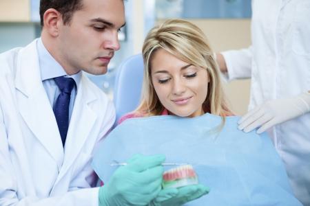 prosthodontics: Dentista mostrando stampo dentale al suo paziente