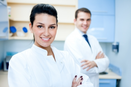 male dentist:  Portrait of pretty female dentist arms crossed with colleague standing in background