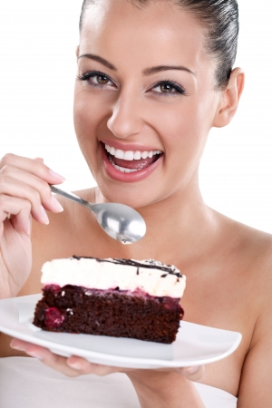 Portrait of smiling woman eating cake, isolated on white background  photo