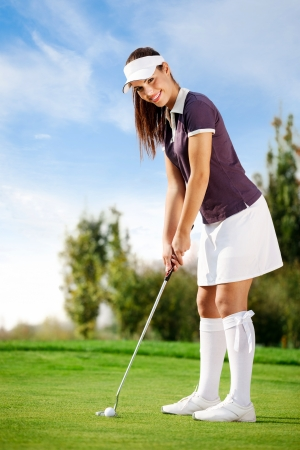 Attractive young woman playing golf  photo