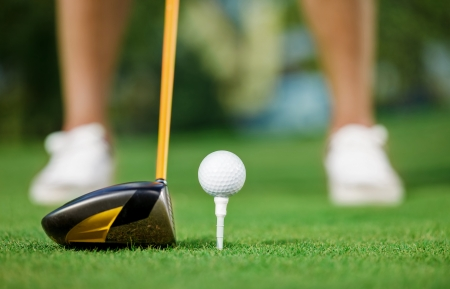 Golf ball and stick with golfer legs in background photo