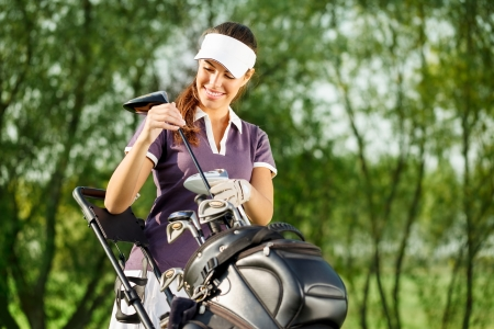 Female golf player outdoors holding a club and smiling Stock Photo - 16861013