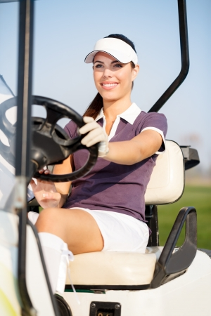 Smiling female golfer driving  golf cart photo