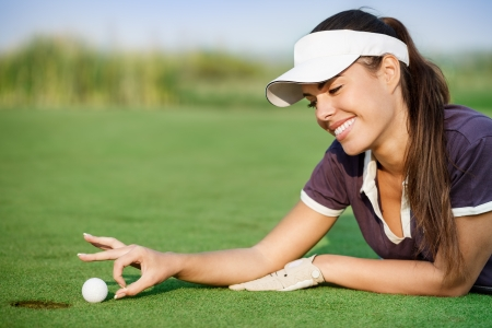 Woman pushing golf ball into the hole Stock Photo - 16860992