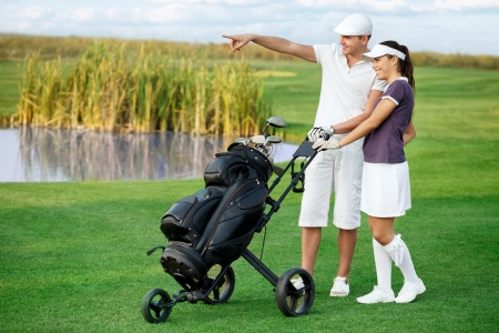 Golfers on golf course, smiling couple man pointing front of them