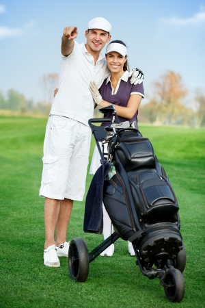Young sportive couple playing golf, man pointing at the best area  Stock Photo - 16861004