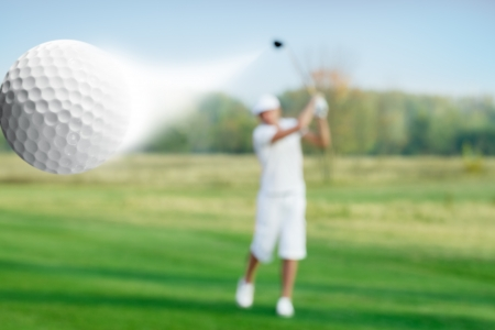golf swings: golfer hitting a flying golf ball Stock Photo