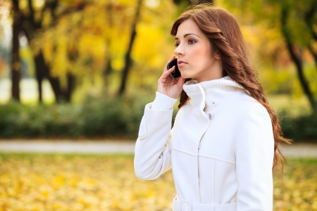 Beautiful young woman using phone in autumn park photo