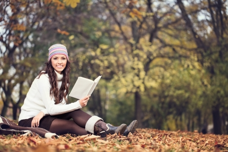 young woman reading book in autumn park Stock Photo - 16860991