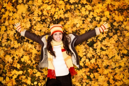 autumn woman lying over leaves and smiling, top view Stock Photo - 16861010
