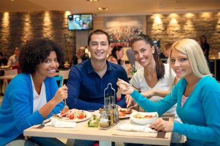 socializando: Grupo de j�venes estudiantes en el almuerzo Foto de archivo