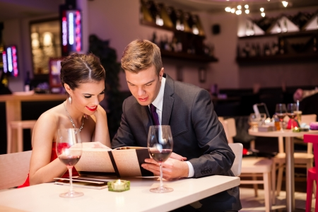 romantic dinner: Smiling couple reading menu  and choosing meal  Stock Photo