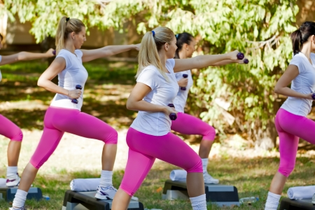 Young women doing exercise with dumbbells photo