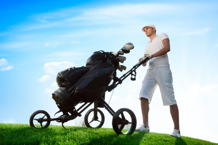 Young golfer on golf course with golf bag photo