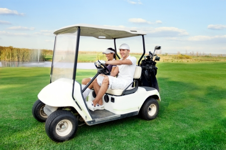 Smiling and happy couple driving a golf-cart with clubs on the back photo