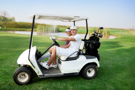 woman golf: Couple in  driving buggy on golf course