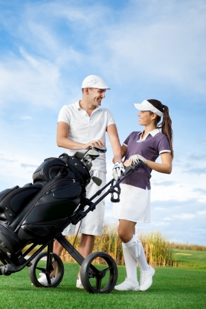 golf glove:  Couple playing golf on a sunny day looking at each other and laughing