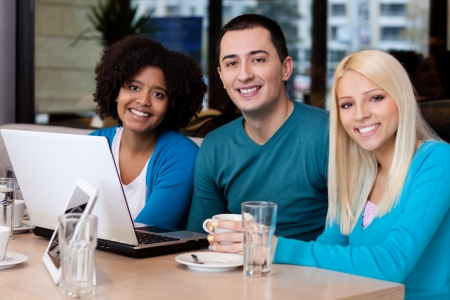 Young friends with laptop in cafe,  smiling and looking at camera photo