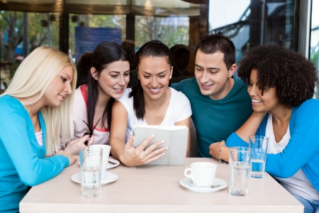 group of teenagers in cafe  using digital tablet photo