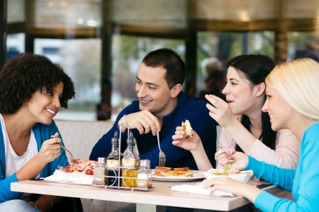 people eating at restaurant:  Four cheerful friends chatting while lunch in restaurant