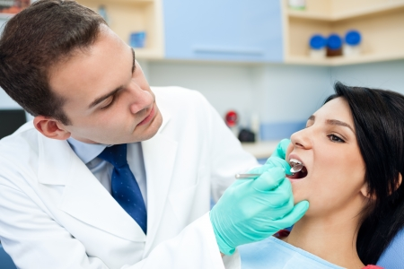 treating:  young man dentist is treating teeth of the patient