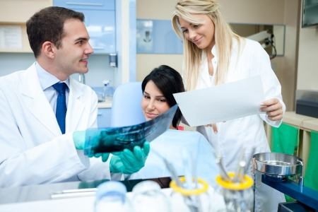 Dentist showing roentgenogram and explaining to patient and assistant Stock Photo - 17803959