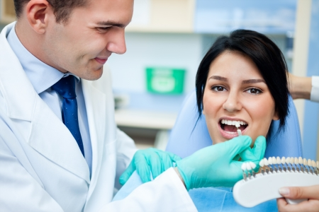 dental medicine: Dentist examining a whiteness of teeth of a patient, and choosing corresponding color
