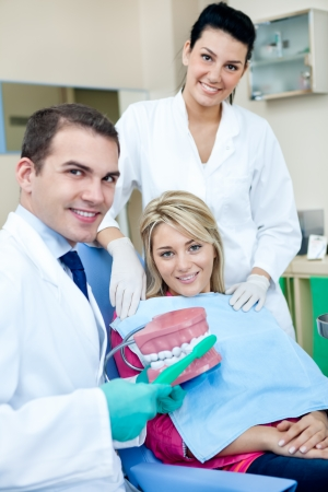 prosthodontics:  Dentist teaching a female patient how to brush teeth