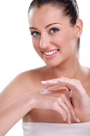 Beautiful smiling woman applying hydrating cream on hands, skincare photo